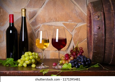 Red and white wine with  grapes beside old cask in wine cellar. Glasses and bottles of wine
