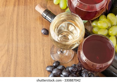 Red and white wine and grapes with fresh leaves on wooden background