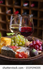 Red and white wine with  grapes on old cask in wine cellar. Glasses and bottles of wine with cheese, jamon, figs and nuts