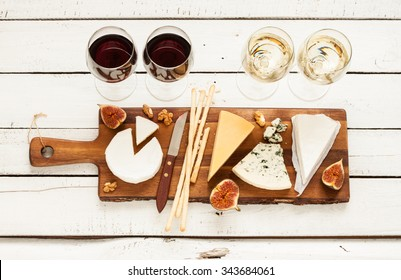 Red and white wine plus different kinds of cheeses (cheeseboard) on rustic wooden table. French food tasting party or feast scenery from above (top view).