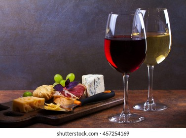 Red and white wine. Smoked cheese, grape, prosciutto, garlic and bread