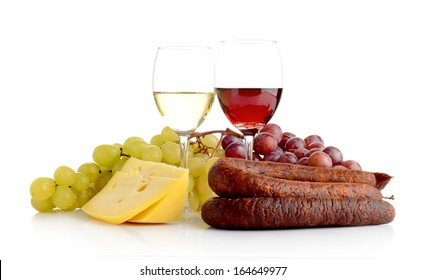 Red and white wine in wineglasses, two bunches of grapes, cheese and sausage isolated on white