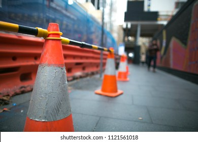 Red and white witches hat cone traffic sign  barrier applying on busy street downtown on pedestrian footpath, road under construction in Sydney city CBD,  Australia