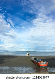 A red and white wooden boat stranded on sandy low tide beach.