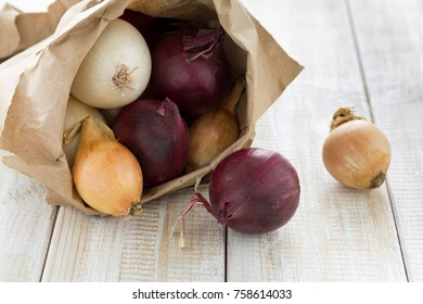 Red, white and yellow onions in a paper bag
