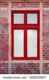 red window on brick facade