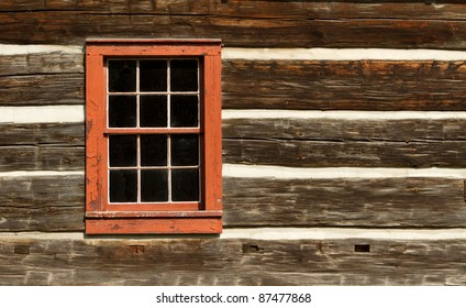 A red window on the wall of a old log cabin.