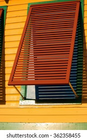 A red window shutter on a yellow building.