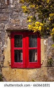 Red window with vintage aspect of an stone house in Galicia,Spain.