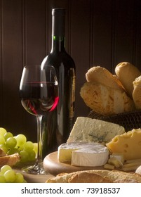Red wine, assorted cheeses, bread and grapes in a still life setup.