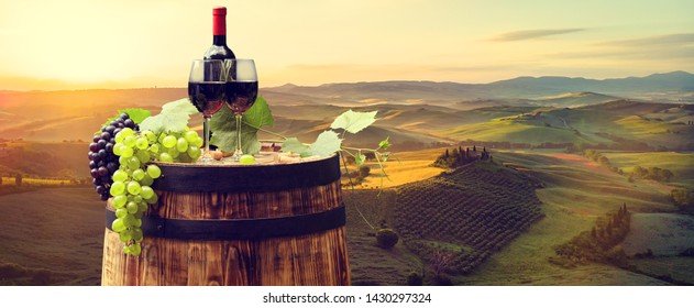 Red wine with barrel on vineyard in green Tuscany. Italy