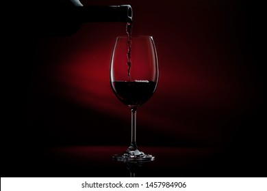 Red wine being poured in a wine glass on a dark red gradient background. Studio close-up shot.