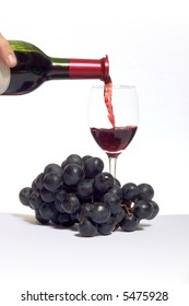 red wine being poured in a glass, with grapes on white