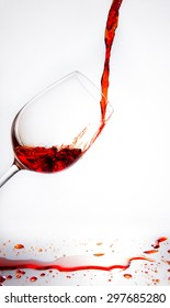 Red wine being poured into glass on white background