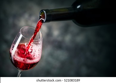 Red wine is being poured into glass shot against dark background
