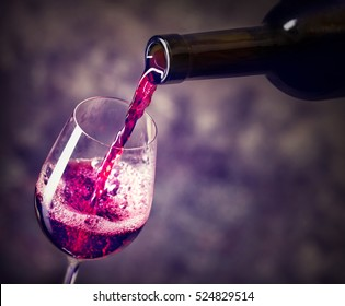 Red wine is the being poured into glass shot against dark background