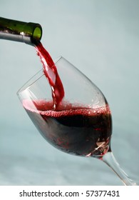 Red Wine being poured into a Wine Glass on a blue background