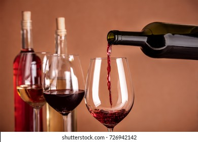 Red wine being poured into a glass from a bottle, on a dark background, with copy space and other glasses and more bottles in the blurred background. Design template for a tasting invitation