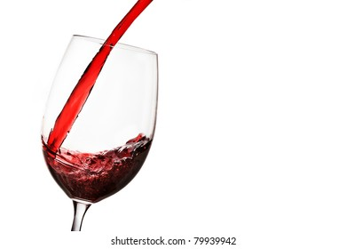 Red wine being poured into wine glass over white.