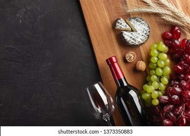 Red wine bottle, bunch of grapes, cheese, ears of wheat and wineglass on wooden board and black background. Top view with copy space.