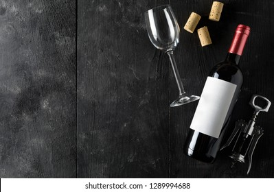 Red wine bottle with corkscrew, corks and wine glass on dark wooden table flat lay from above with copy space