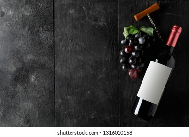 Red wine bottle with corkscrew and grapes on dark wooden table flat lay from above with copy space