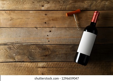 Red wine bottle with corkscrew on brown rustic wooden table flat lay from above with copy space