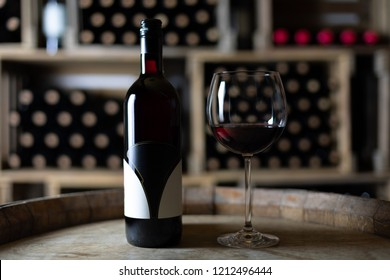 red wine bottle with a filled wineglass on a barrel in a cellar, switzerland