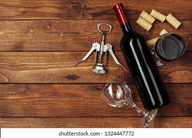 Red wine bottle, wine glass and corkscrew on wooden table background