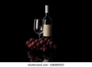 Red wine bottle and glass with grape on the black background