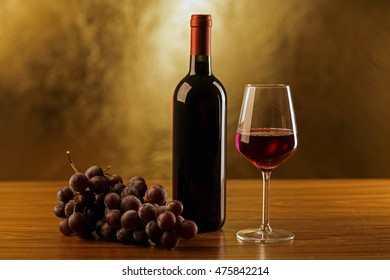 Red wine bottle with glass and grape on gold background