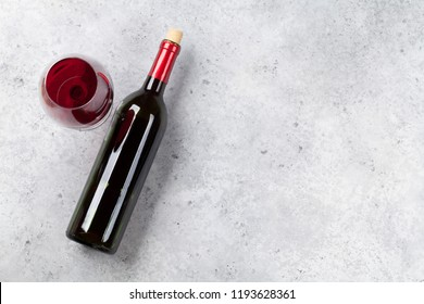 Red wine bottle and glass lying on stone backdrop. Top view with space for your text