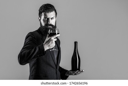 Red wine in bottle, wine glass. Red wine in a glass. Man holding bottle with champagne, wine. Beard man, bearded, sommelier, tasting. Sommelier man, degustator, winery. Black and white.