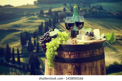 Red wine bottle and wine glass on wodden barrel. Beautiful Tuscany background.