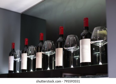 Red wine bottle with glass on shelf