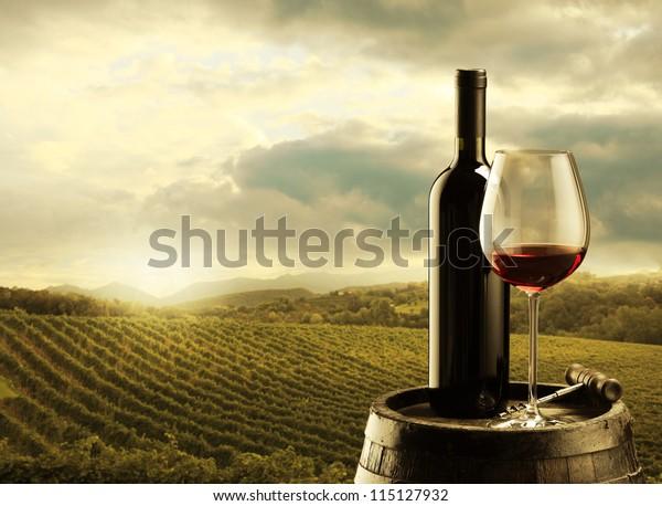 rote Weinflasche und Weinglas auf Holzfass