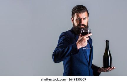 Red wine in bottle, wine glass. Sommelier man, degustator, winery. Man holding bottle with champagne, wine. Bottle, red wine glass. Beard man, bearded, sommelier, tasting.