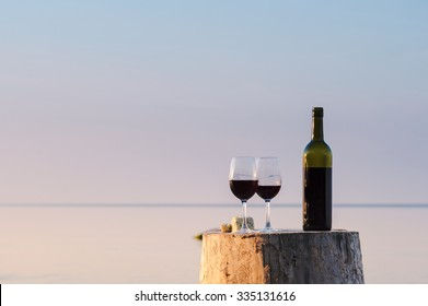 Red wine bottle and wine glasses on the shore in evening