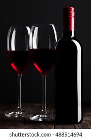 Red wine bottle and glasses on wooden table black background