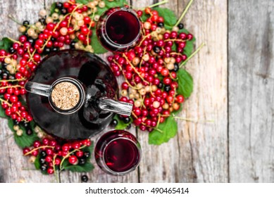 Red wine bottle and glasses of wine, overhead. Seasonal homemade alcohol made from currant