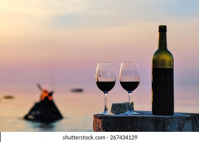 Red wine bottle and wine glasses at the sea