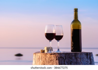 Red wine bottle and wine glasses at the seashore
