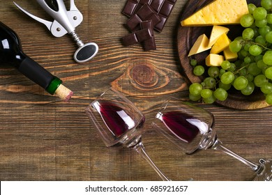 Red wine bottle, grape, cheese and glasses over wooden table. Top view with copy space