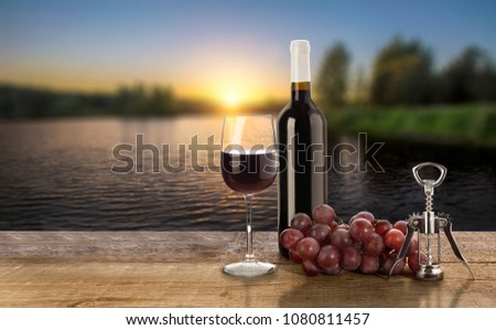 Red wine bottle, grape, corkscrew  and wine glass on sunset background