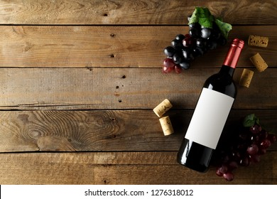 Red wine bottle with grapes and corks on brown rustic wooden table flat lay from above with copy space