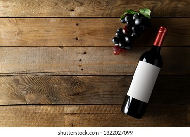 Red wine bottle with grapes on brown rustic wooden table flat lay from above with copy space