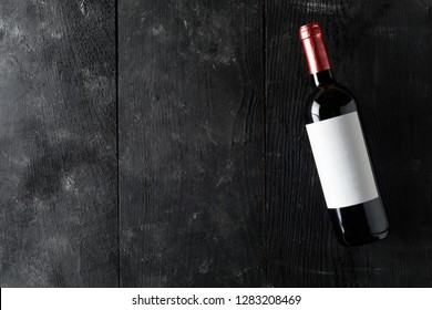 Red wine bottle on dark wooden table flat lay from above with copy space