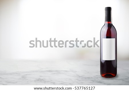 Red wine in bottle on white marble table.