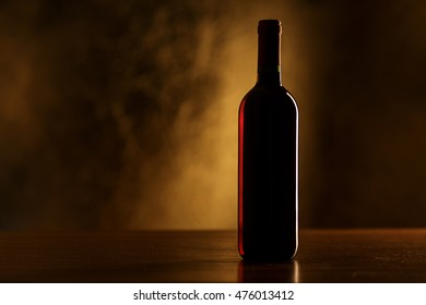 Red wine bottle on wooden table and dark background - silhouette