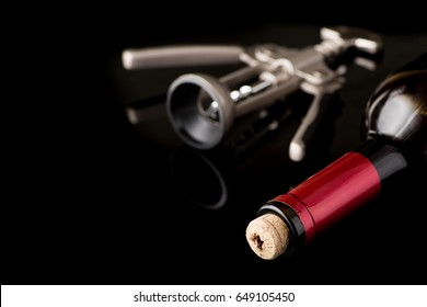 Red wine bottle open with corkscrew isolated on a black background